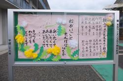 正門の掲示板にタンポポの詩が掲示されています。