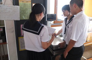 昼休みに,各学年の給食部の生徒たちが温食缶・ご飯・個食の食缶と献立ごとに計量します。